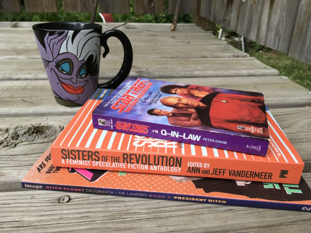 A stack of books consisting of Bitch Planet vol. 2 by Kelly Sue DeConnick, Sisters of the Revolution anthology, and Q-in-Law from the Star Trek Next Generation series. Also, an Ursula mug from Little Mermaid