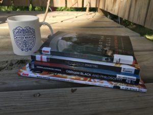 A stack of four books next to a Bitch Media mug